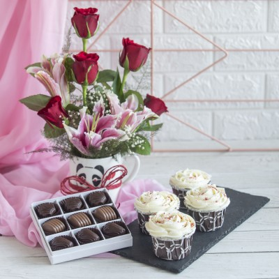 4 Red velvet Cup Cakes , Box  of 9 chocolate  Pralines and Arrangement of Red Roses and lilies in a mug