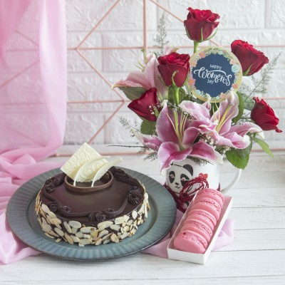 Chocolate almond Dutch truffle cake , Box of 5 Macarons and Arrangement of Red Roses and lilies in a mug with a Blue Women's Day Topper