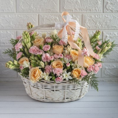 White Cane Basket of Tube Roses, Pink Spray Carnation And Peach Roses