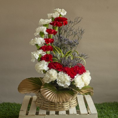 Arrangement of Red and white Carnations with Golden leaves in a Basket
