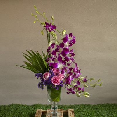 Arrangement of Orchids and Pink Roses and Limonium in a Vase